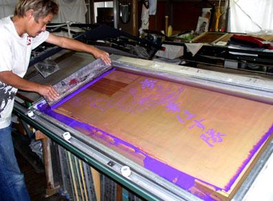 大プリントはこんなに大きな版でプリントします。 裁断した白生地に紫色でプリント中。